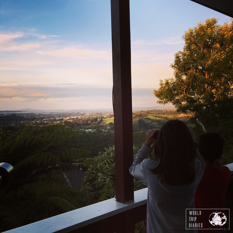Two boys looking at the landscape with binoculars. Auckland is a great place to visit with kids - click for more!