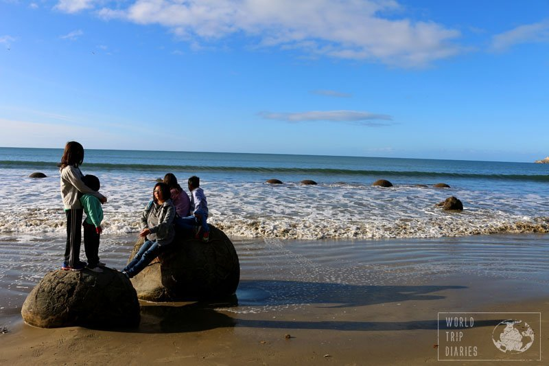 2 round boulders half sunk in the sand of the beach at Moeraki beach, in NZ, and 2 kids standing on one and 3 people sitting on the other. Moeraki is a wonder!