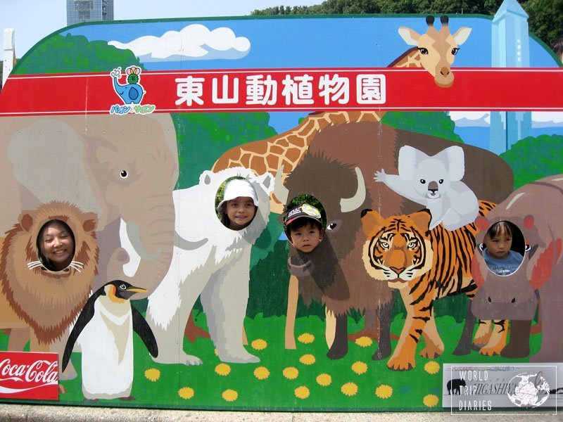 The mom and the 3 older kids in photo spot where we put our faces in the holes to look like we were the animals at Hoshigaoka Zoo in Nagoya, Japan.