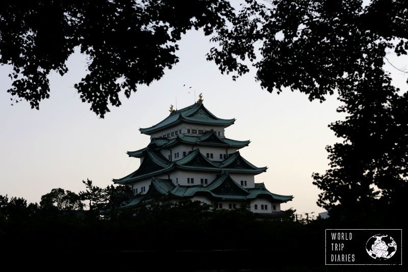 Nagoya Castle at sunset with the tree leaves framing it. It's a beautiful place and the gardens surrounding the castles are the best part for families.