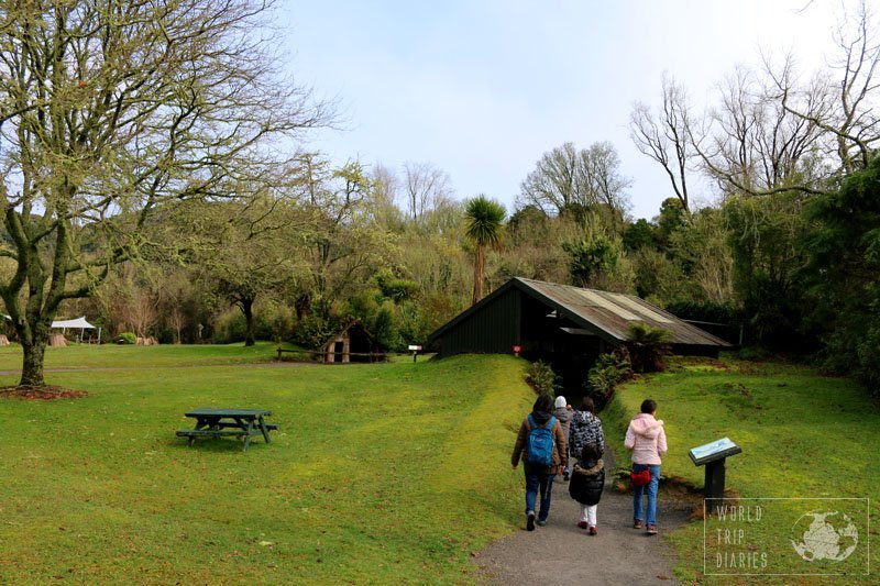 5 of us walking toward a half buried house - real thing - in The Buried Village of Te Wairoa, Rotorua (NZ). The lava from Mount Tarawera really did it.