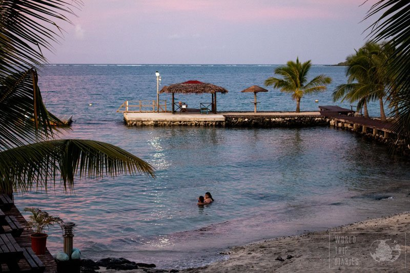 The pink and blue sunset over a beach in Samoa. Samoa is an incredible family travel destination. There's a little for every kind of traveler. Find out more!