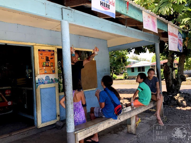 Dad and the kids resting in front of a store in Savai'i. We stopped to grab something to drink. The stores are almost always simple but they have a bit of everything. Click for more!