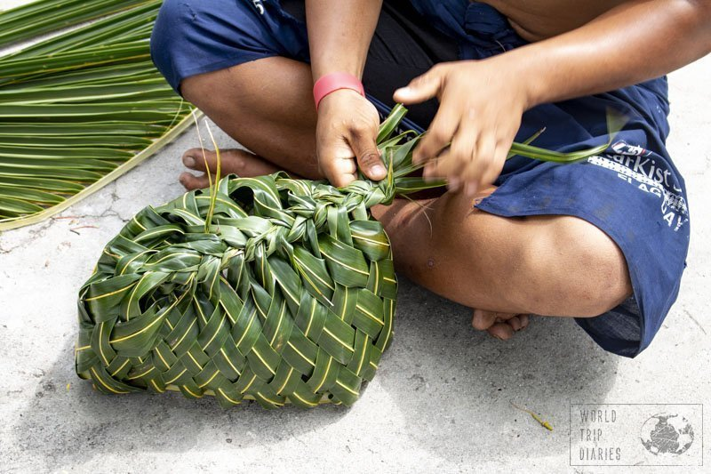 A man weaving a coconut tree leaf basket. They're very common in Samoa, just as anything woven from coconut tree leaves! Click for more!