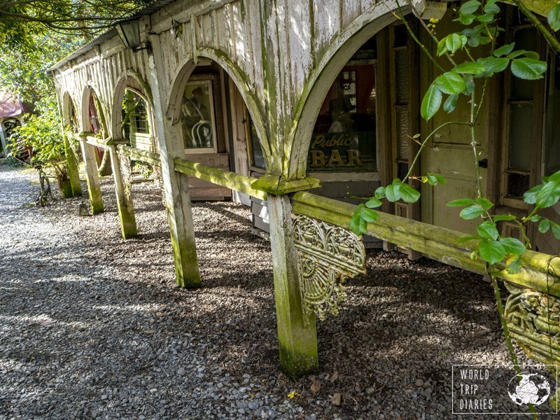 The wooden arches of a veranda, with plants dangling from them at Demolition World, NZ.