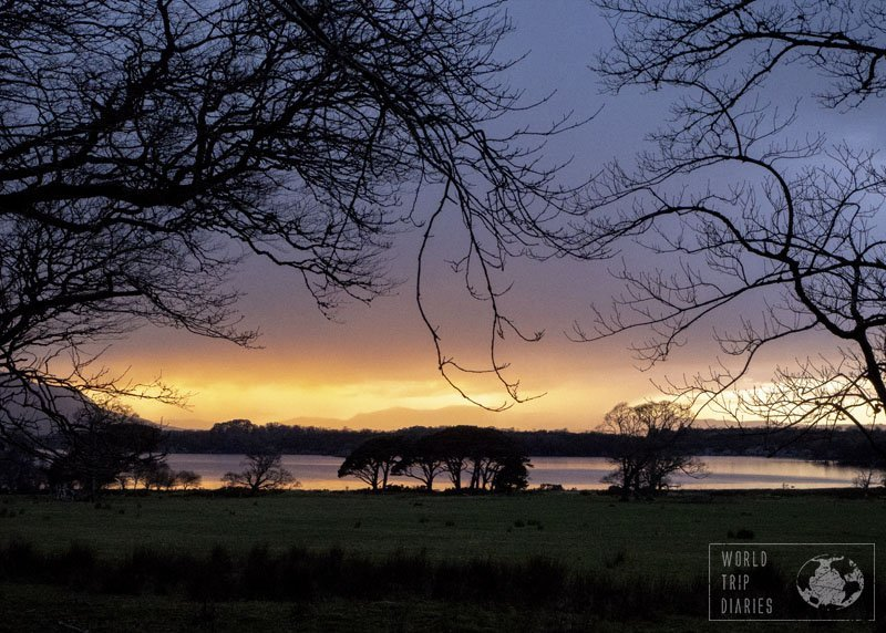 A sunset on the back, reflecting on the lake and trees in the front. That's Lake Muckross, in Ireland, and its stunning sunsets. Click for more!