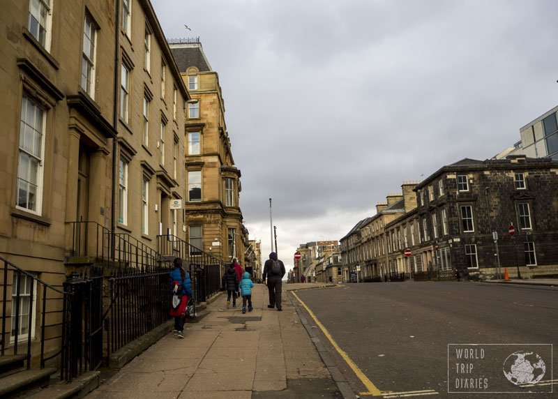 The dad and the kids walking on a street in Glasgow, Scotland, with its buildings around. Glasgow is very walkable and it's delightful!