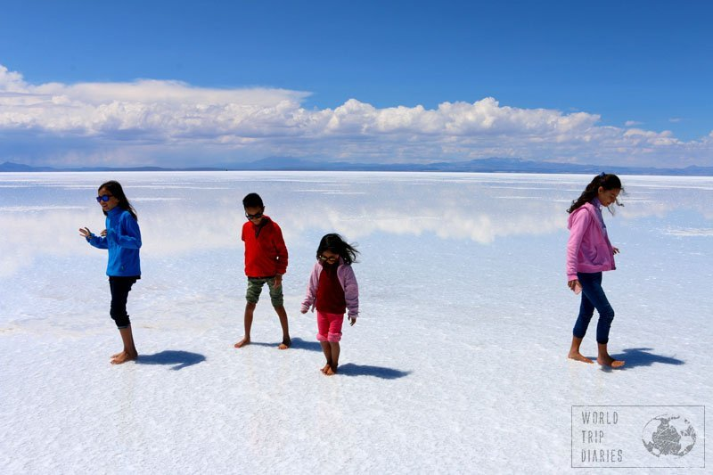 4 kids walking on the salt flats in Bolivia. The white floor is reflecting the clouds. The dreamiest place in the whole world!