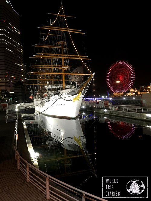 A night shot of a ship and the Ferris wheel reflecting on the water. Yokohama is a beautiful city, very worth the visit while in Japan.
